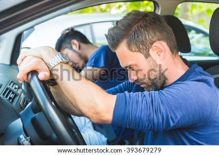 A bored man in the car stuck in the traffic. A couple of tired friend sitting in the car and trying to rest while driving to vacations destination or during any travel. - stock photo