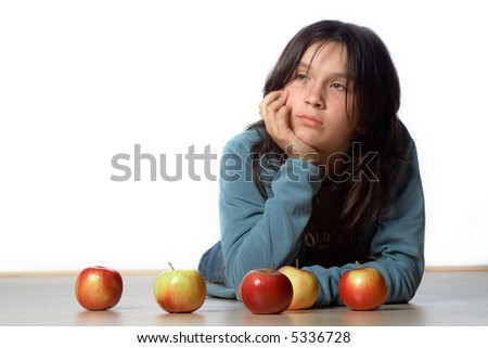 A bored teenaged girl props her head up with her hand behind 5 apples.