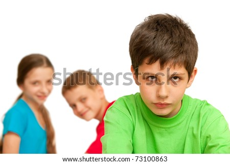 A boring kid is sitting against his happy friends; isolated on the white background - stock photo