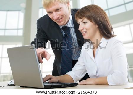 A boss and a secretary, a secretary uses laptop - stock photo
