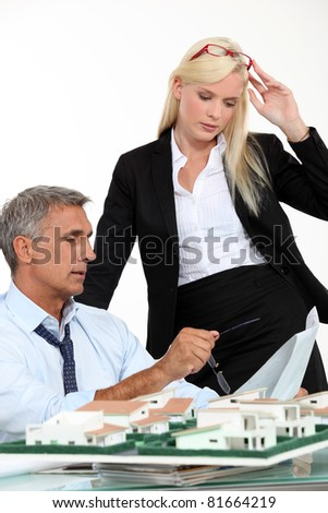 a boss and his female assistant thinking behind a subdivision model - stock photo