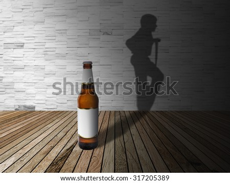 A bottle alcohol into a dark room with its Man injured silhouette shadow on a brick wall. - stock photo