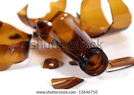 A bottle broken into many pieces on a white surface - stock photo