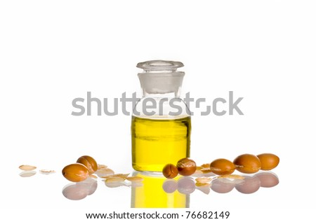 A bottle of argan oil on white background with argan fruits. - stock photo