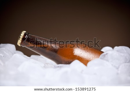 A bottle of beer buried on ice. - stock photo