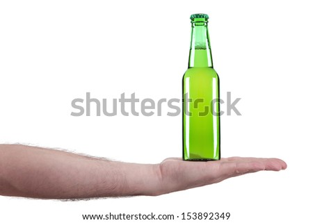 A bottle of beer in the palm of a hand. - stock photo