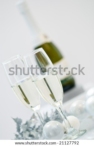 A bottle of champagne and two filled glasses with Christmas baubles - stock photo