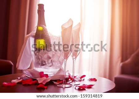 A bottle of Champagne and two glasses with romantic rose petals.