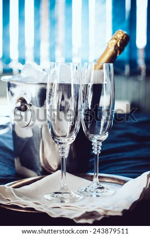 A bottle of chilled champagne in an ice bucket and two glasses on a bed, in front of window curtains. - stock photo