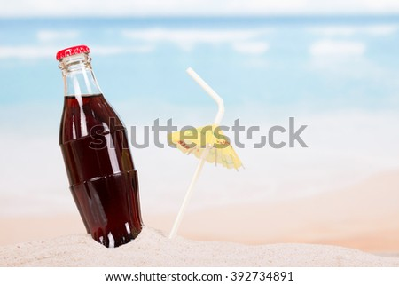 A bottle of cola in the sand on the seashore. - stock photo