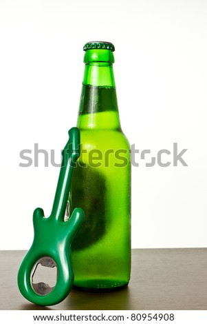 A bottle of cold beer with the guitar opener - stock photo