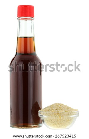 A bottle of cold pressed Sesame oil next to a bowl of white Sesame seeds, isolated on white background - stock photo