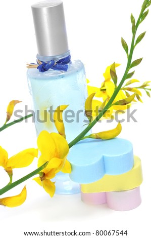 a bottle of fresh scent, yellow flowers and heart-shaped soaps on a white background - stock photo