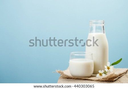 A bottle of milk and glass of milk on a wooden table on a blue background, tasty, nutritious and healthy dairy products - stock photo