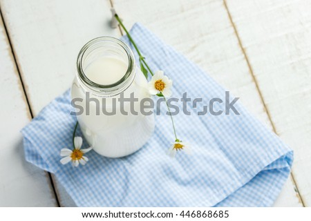 A bottle of milk with Napery on a white wooden table