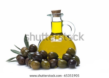 A bottle of olive oil and a lot of olives. - stock photo