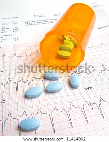 a bottle of pills on a EKG strip - stock photo