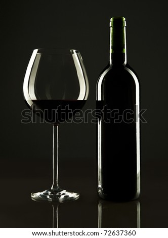 A bottle of red wine and a glass with it on a dark black background - stock photo