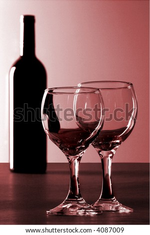 A bottle of red wine and 2 glasses shot under low lighting.  The bottle is in the background and the 2 glasses are the focus. The glasses are empty.