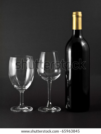 A bottle of red wine and two elegant glasses on black background - stock photo