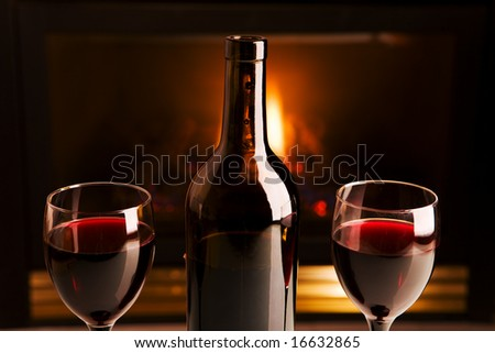A bottle of red wine and two glasses in front of a fireplace - stock photo