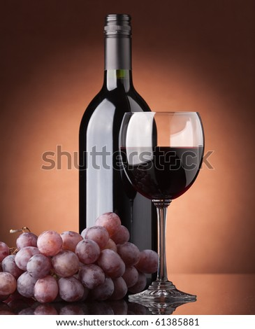 A bottle of red wine, glass and grapes on a brown background - stock photo