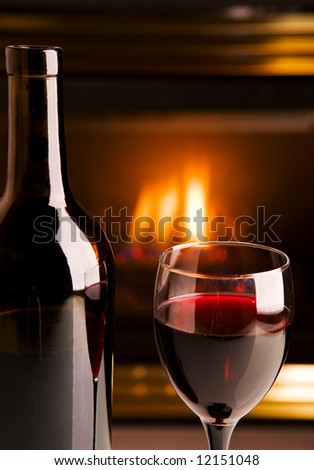 A bottle of red wine in front of a fireplace