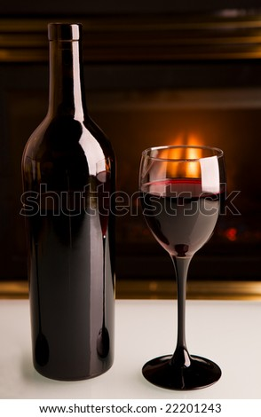 A bottle of red wine in front of a fireplace on a white table - stock photo