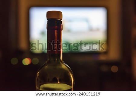 A bottle of red wine in front of the TV at night - stock photo