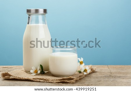 A bottle of rustic milk and glass of milk on a wooden table on a blue background, tasty, nutritious and healthy dairy products - stock photo