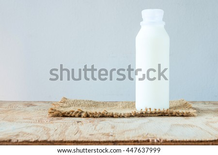 A bottle of rustic milk on a wood table on white background, tasty, nutritious and healthy dairy products - stock photo