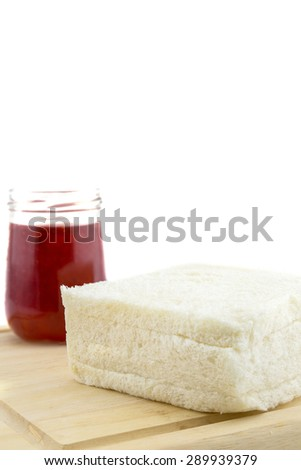 A bottle of strawberry jam and bread