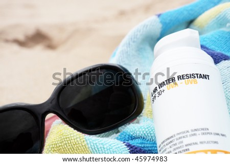 A bottle of sunscreen and pair of sunglasses on a beach towel. Sandy background. - stock photo