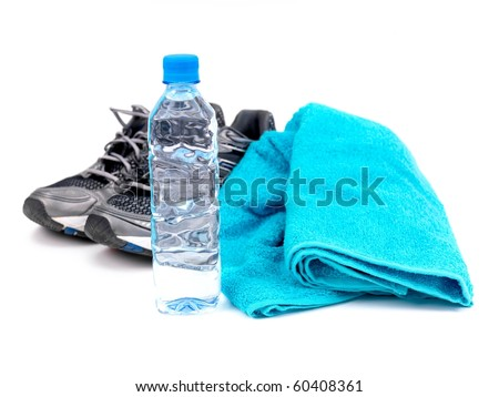 A bottle of water, joggers and a sports towel isolated against a white background - stock photo