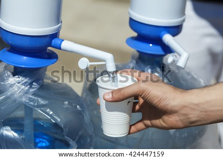 a bottle of water with pomp. hand holding pours water  plastic glass  - stock photo
