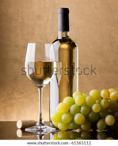 A bottle of white wine, glass and bunch of grapes on a golden background - stock photo