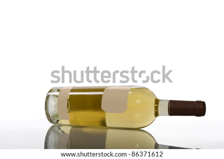 A bottle of white wine with blank labels lying on its side with its reflection below.  White background with plenty of copy space - stock photo