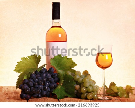 A bottle of white wine with grapes and leaves on wooden background - stock photo