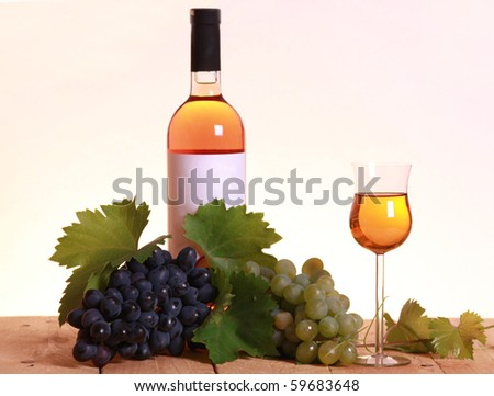 A bottle of white wine with grapes and leaves on wooden background. Focus on wineglass. - stock photo