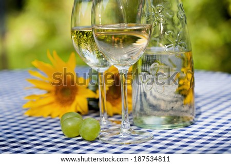 A bottle of wine with two filled glasses - stock photo