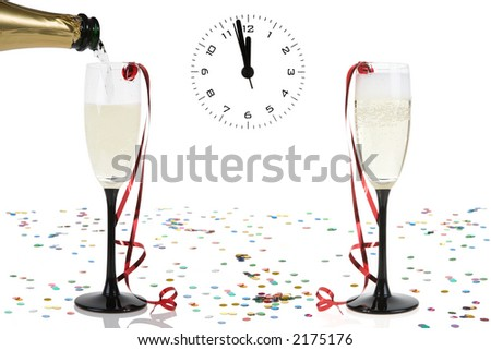 a bottle pours a glass of champagne and a clock on the verge of midnight - stock photo