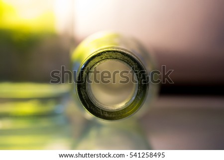 A bottle spout in macro with green gleams from the back.