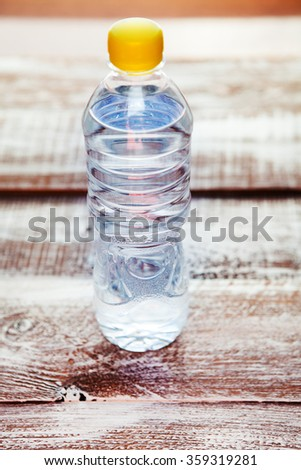 a bottle with water is isolated on a wooden background - stock photo