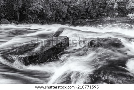 A boulder in the middle of the Raquette River amidst the rapids of Buttermillk Falls in the Adirondacks Mountain of New York - stock photo