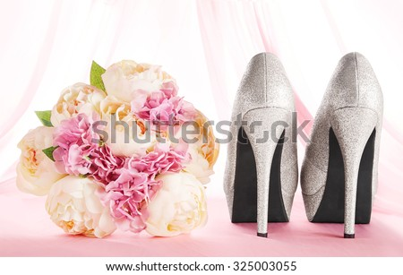 A bouquet and brilliant silver shoes. Wedding bridal fashion image. Curtain background on the pink floor. - stock photo