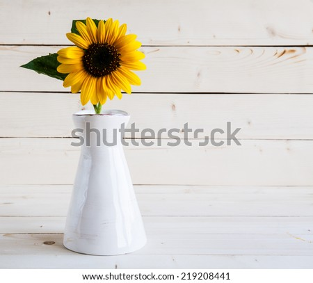 A bouquet of autumn sunflowers in a vase on a grungy wooden table. - stock photo