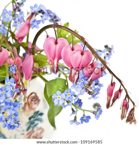 A bouquet of bleeding hearts and forget me nots in a small pottery vase. - stock photo