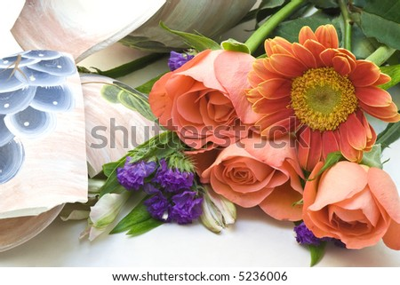 A bouquet of flowers and a broken vase close-up - stock photo