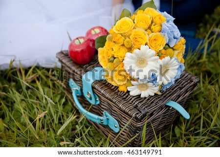 a bouquet of flowers and apples on the picnic basket