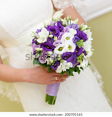 A bouquet of flowers at a wedding in the hand of the bride. - stock photo